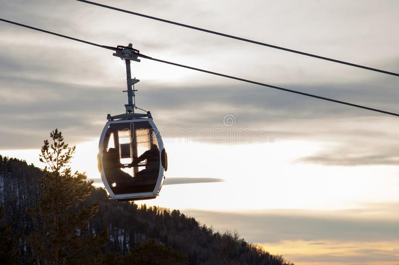 A gondola cableway with a booth suspended on a cable in which a couple in love sits on a background of mountains, trees and sunset royalty free stock photo