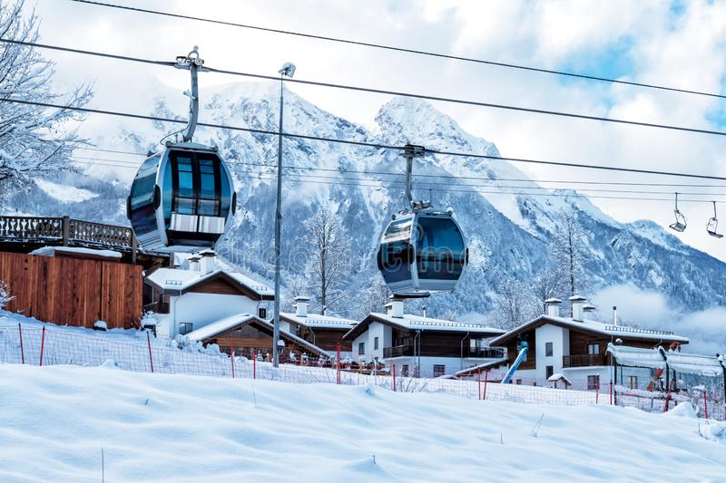 Gondola lifts, village and high mountain range on a clear sunny day in winter. Gondola lift, village and high mountain range on a clear sunny day in winter stock photo