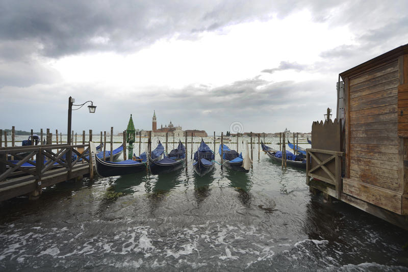 Gondola park on Venice. Gondola floating oposite a bascilica on the Island lagoon Venice royalty free stock photo