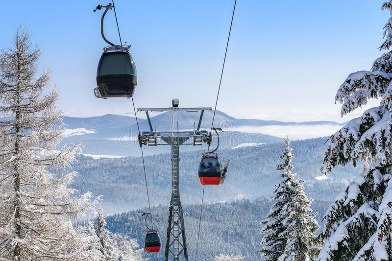 Gondola ski lift in the mountains. Gondola cabin lift in the ski resort over the forest on the background of snowy mountains in sunny day high details royalty free stock photos