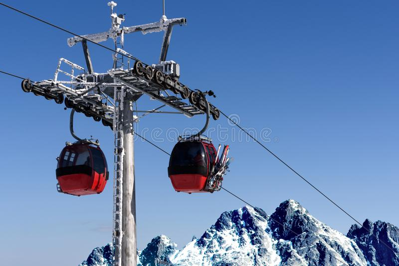 Gondola ski lift in the mountains. Gondola cabin lift in the ski resort over the high mountains on the blue sky background in sunny day with copy space stock photo