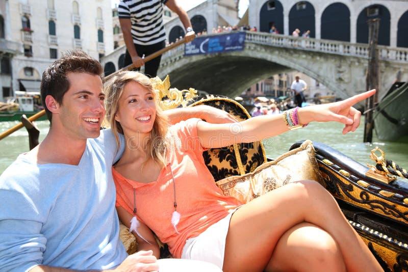 Gondola tour. Couple on a Gondola ride passing by Rialto bridge, Venice stock photos