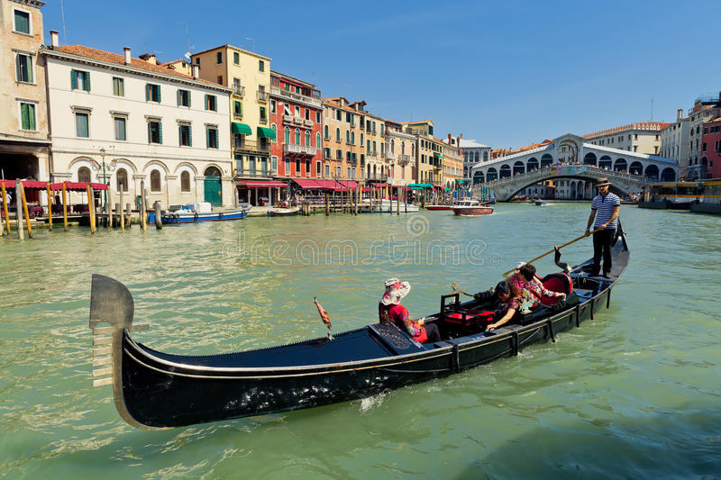 Gondola with tourists near Rialto Bridge in Venice royalty free stock image