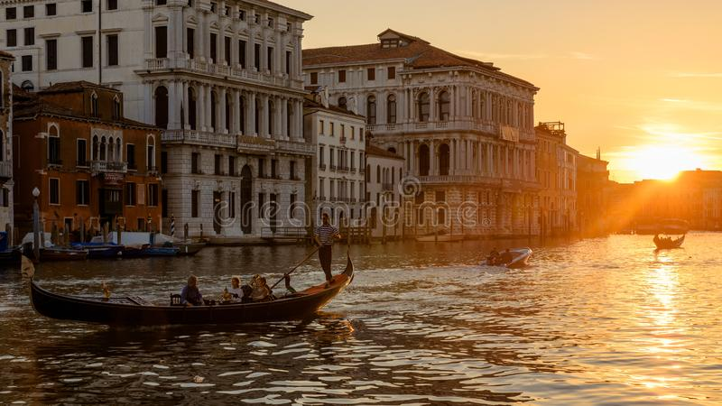 Gondola with tourists sails on Grand Canal at sunset in Venice. Scenery of town at summer night royalty free stock image