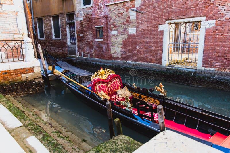 Gondola tradizionale decorata in rosso ed in dorato in un canale di verde di Venezia, Italia fotografia stock libera da diritti