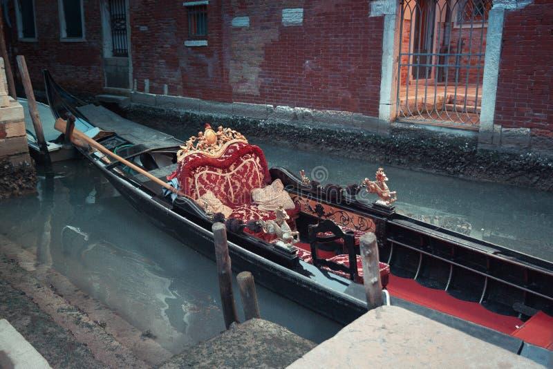 Gondola tradizionale decorata in rosso ed in dorato in un canale di verde di Venezia, Italia immagine stock libera da diritti