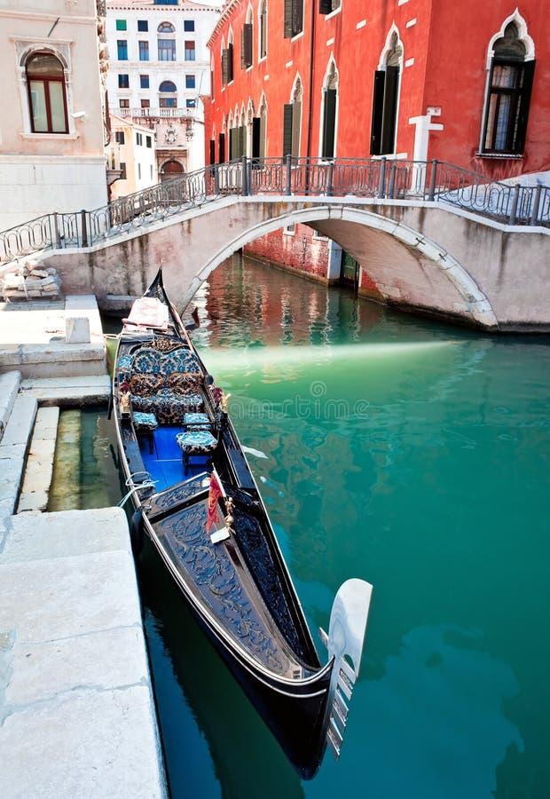 Gondola on Venice canal with bridge stock photography