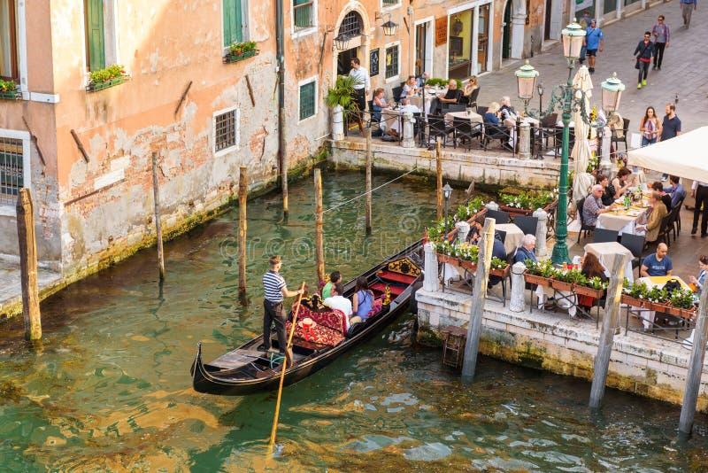 Gondola z ludźmi zbliża ulicznej kawiarni w Wenecja, Włochy obraz stock