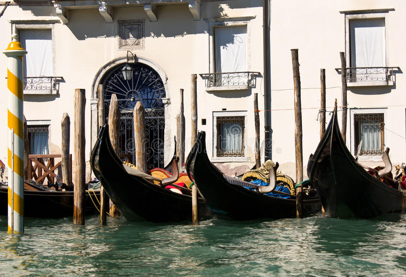 Gondolas, the cars of Venice Italy. The famous gondolas, the symbol of Venice, Italy, parked in front of a building stock photography
