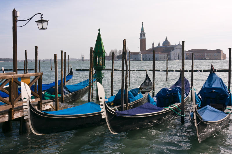 Gondolas moored by Saint Mark's square in Venice. Gondolas moored by Saint Mark square with San Giorgio di Maggiore church in the background - Venice, Venezia royalty free stock image
