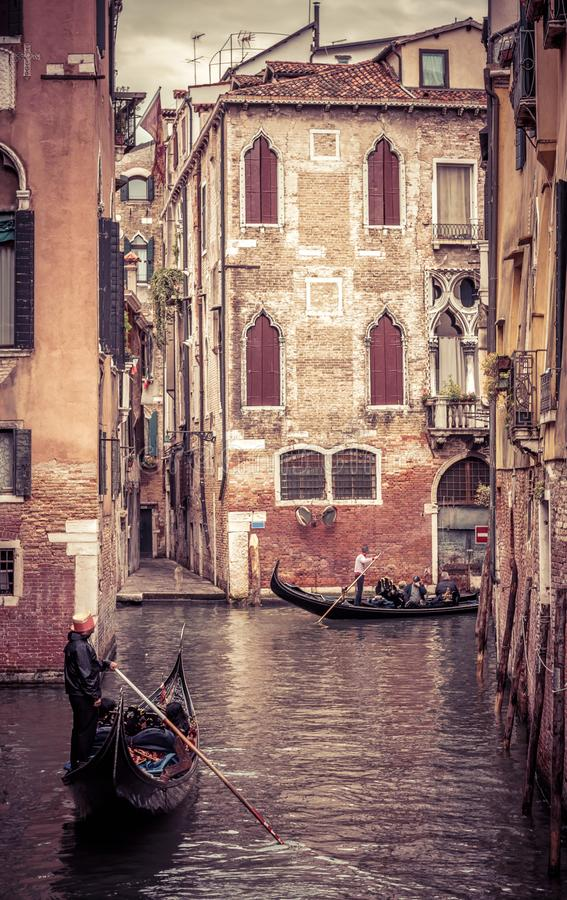Gondolas with people sail in Venice, Italy. Vintage view of a narrow street of Venice. Old flooded alley with ancient Venice houses. Romantic water trip on a stock photo