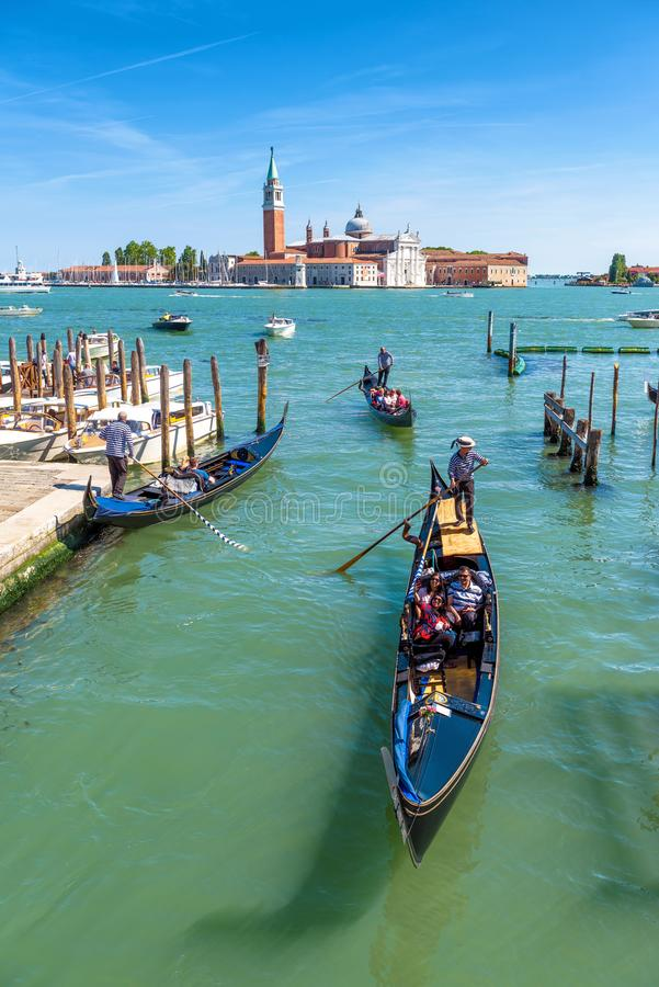 Gondolas with tourists are sailing in Venice royalty free stock images