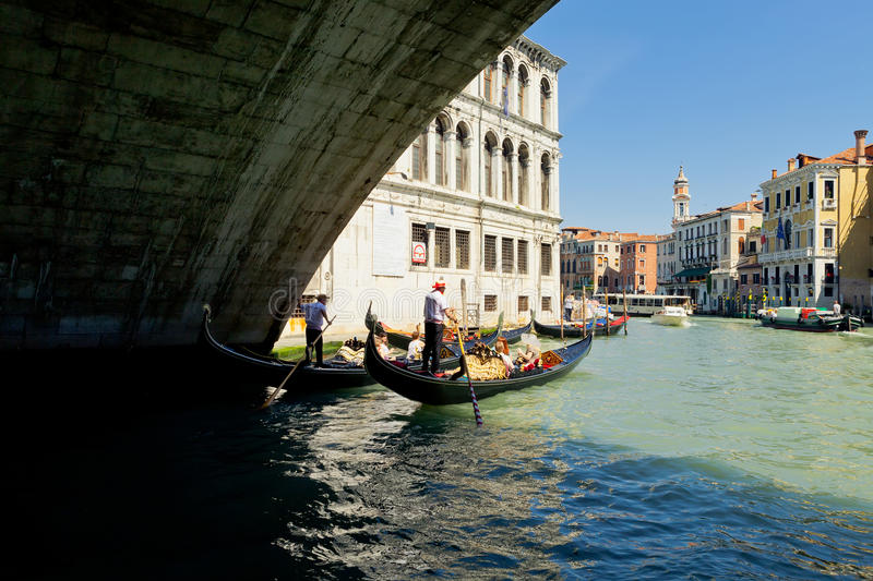 Gondolas under Rialto bridge in Venice, Italy stock image