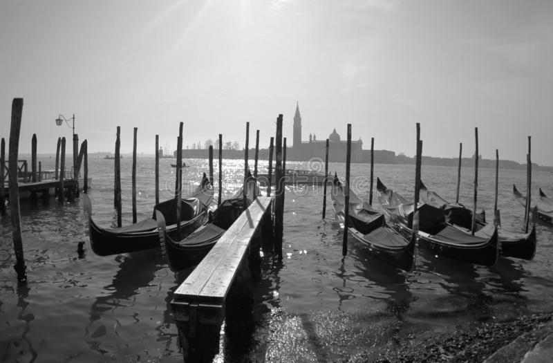Gondolas in Venice with church in the background.Black and White photo. stock photos