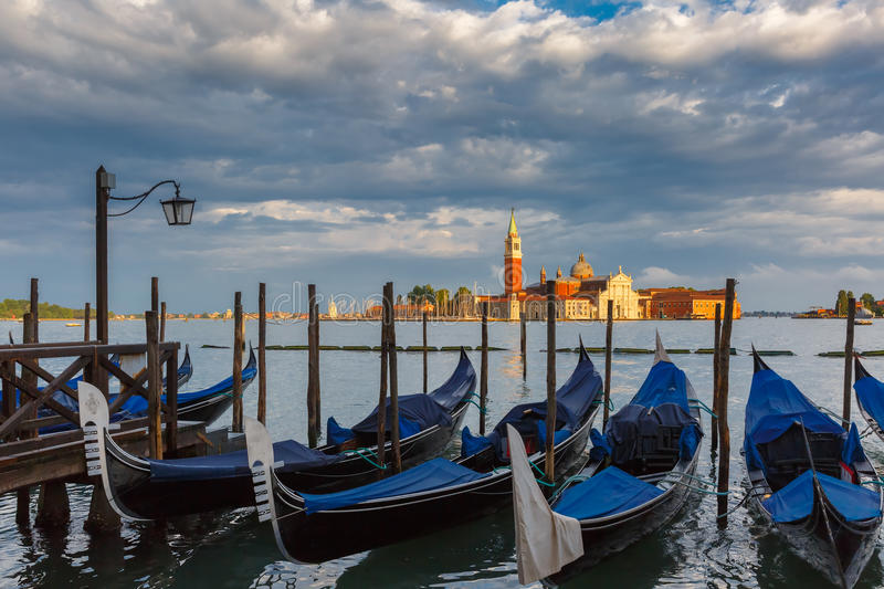 Gondolas in Venice lagoon after the storm, Italia. Gondolas moored by Saint Mark square with San Giorgio di Maggiore church in the background in Venice lagoon stock images
