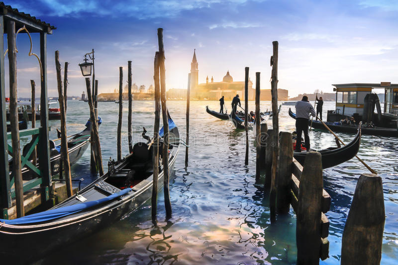 Gondolas in Venice and sunset behind San Giorgio Maggiore church royalty free stock photography