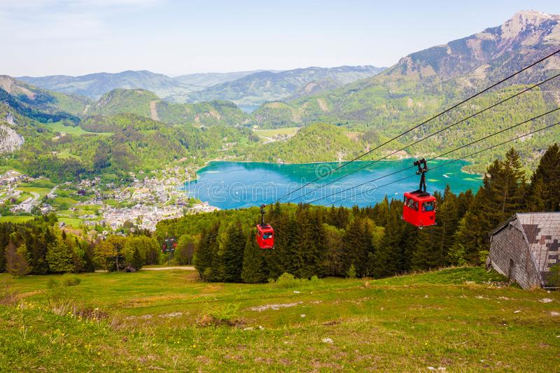 Gondolas of Zwoelferhorn Seilbahn cable way and a view of alpine village St.Gilgen and Wolfgangsee lake, Austria royalty free stock photo