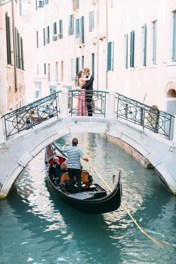 Gondole in chanel of Venice, Italy. Lovers hugging and kissing stand on the bridge of the canal royalty free stock photography