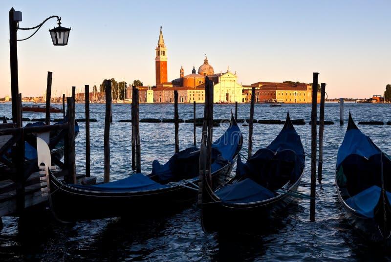 Gondole, San Giorgio Maggiore, sunset Venice, Italy. Streetlighy, Gondola or gondole in the Canal Grande in front of the San Giorgio Maggiore Benedictine church stock photography