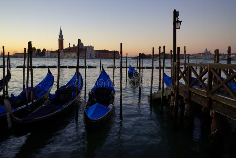 Gondole Stazio Danieliin en salida del sol, con la iglesia de San Giorgio Maggiore en el fondo Venecia, Italia imagen de archivo libre de regalías