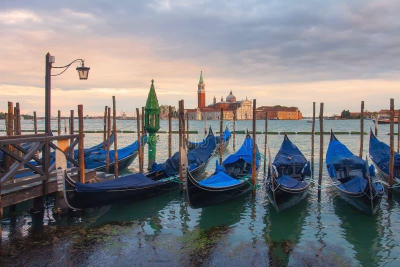 Gondoler i den Venedig sikten på den San Giorgio Maggiore kyrkan från den San Marco fyrkanten i Italien royaltyfria bilder