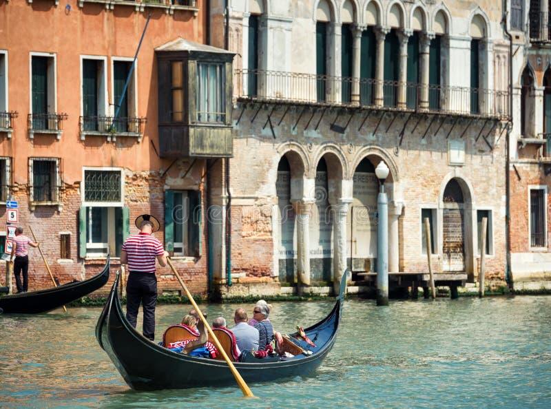 Gondoler med turister i Venedig arkivbild