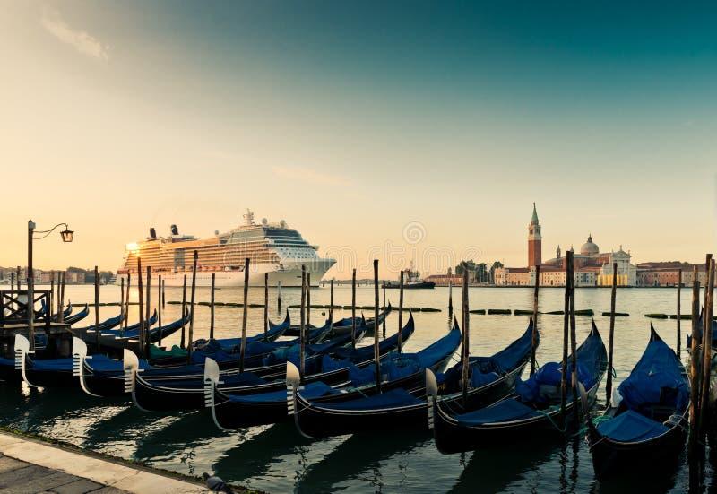 Gondoler på bakgrunden av det enorma kryssningskeppet i Venedig arkivfoto