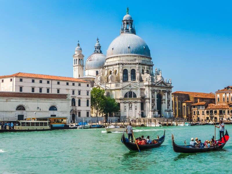 Gondoler på kanalen som är stor med basilikadi Santa Maria, Venedig, Italien royaltyfria bilder