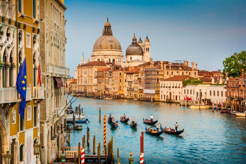 Gondoler på kanalen som är stor med Santa Maria della Salute på solnedgången royaltyfri bild
