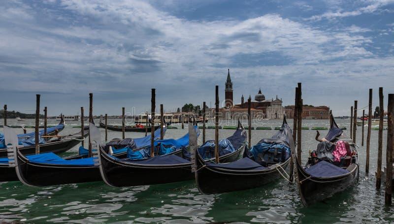 Gondoler som förtöjas av den St Mark fyrkanten med San Giorgio di Maggiore, kyrktar i Venedig, Italien royaltyfria foton