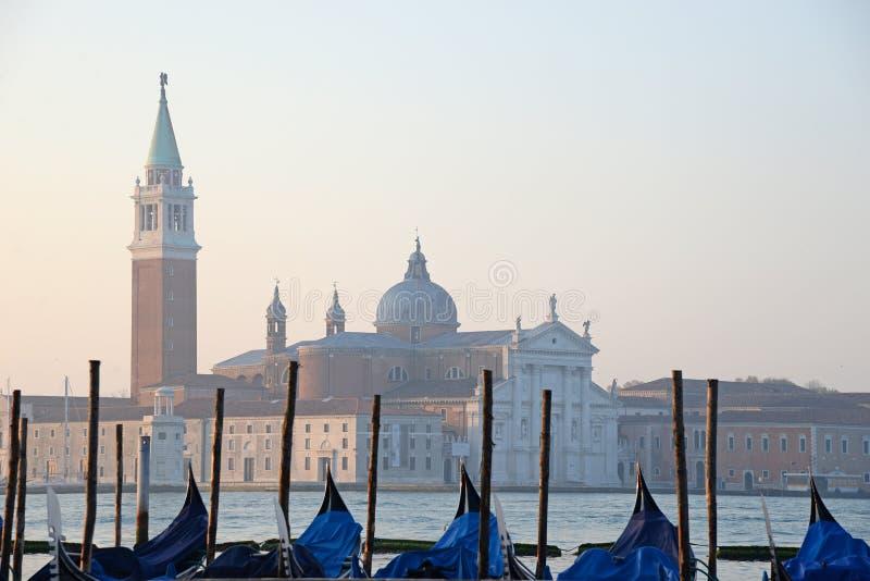 Gondoler som förtöjas av Sanktt Mark, kvadrerar med den San Giorgio di Maggiore kyrkan i bakgrunden - Venedig, Venezia, Italien,  royaltyfria bilder