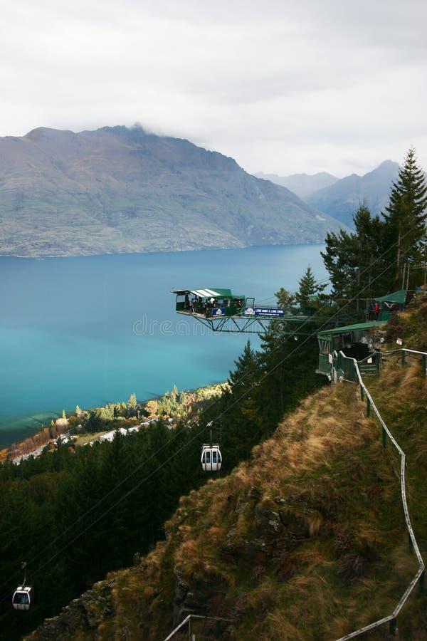 Gondoler som passerar den bungy hoppplattformen, inställde i midair med hisnande sikt av sjön och berg royaltyfria foton