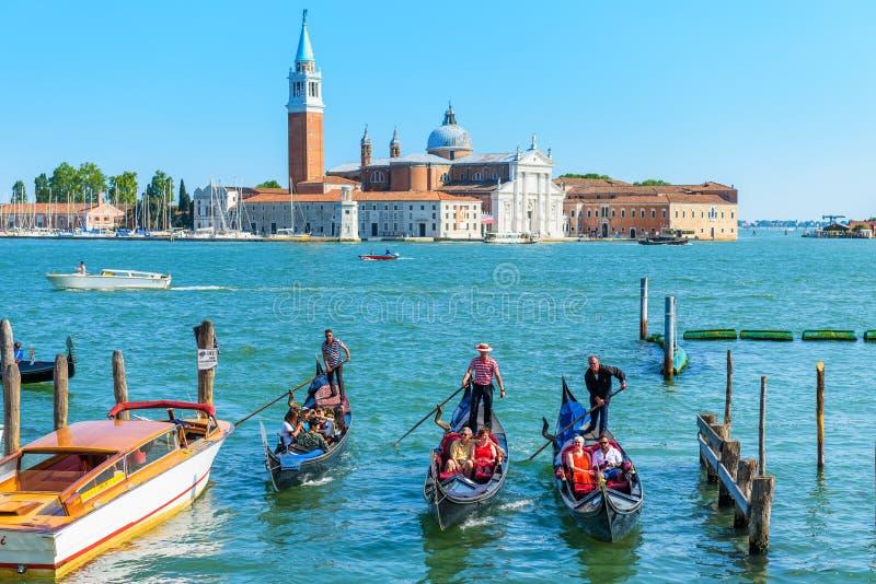 Gondolerna med turister i Venedig arkivbild