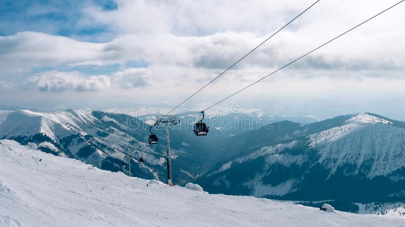 GONDOLI dźwignięcie Kabina dźwignięcie w ośrodku narciarskim Yasna przy świtem z halnym szczytem w odległości Zimy narciarstwo i  zdjęcie stock