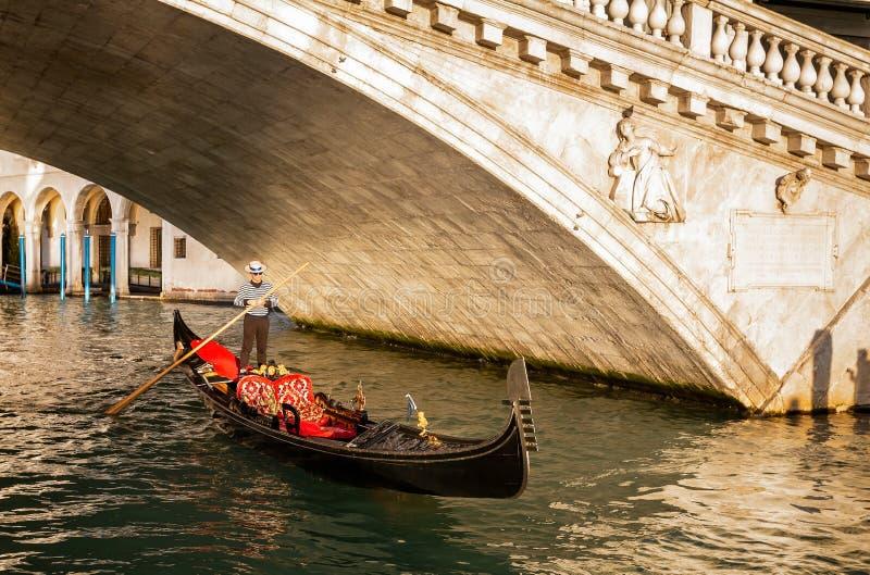 Gondoli omijanie pod kantora mostem przy zmierzchem w Wenecja, Włochy obrazy stock
