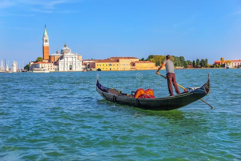 Gondolier που πλέει στο νησί SAN Giorgio Maggiore στην ενετική λιμνοθάλασσα στοκ εικόνες