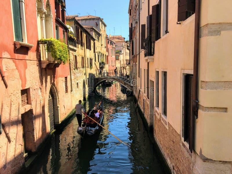 Gondolier принимает его гондолу вполне туристов вниз с узкого небольшого пустого канала стоковые фотографии rf