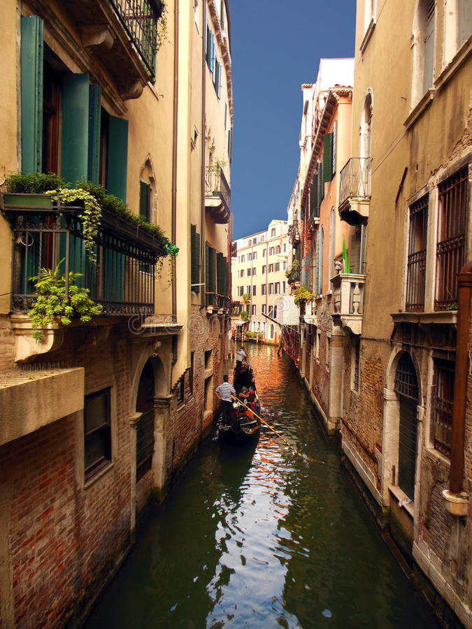 Gondolier. A gondolier dressed in a traditional striped shirt, transports tourists down one of the many picturesque canals in Venice, Italy royalty free stock photography
