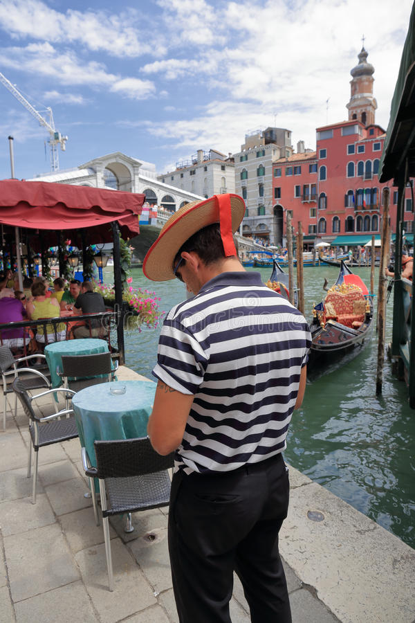 Gondolier on the pier. VENICE, ITALY - 26 JUNE, 2014: Gondolier on the pier. The profession of gondolier is controlled by a guild, which issues a limited number stock photography