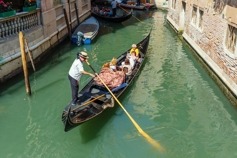Gondolier rides gondola on the canals of Venice. VENICE, ITALY - 26 JUNE, 2014: Gondolier rides gondola. The profession of gondolier is controlled by a guild stock photography