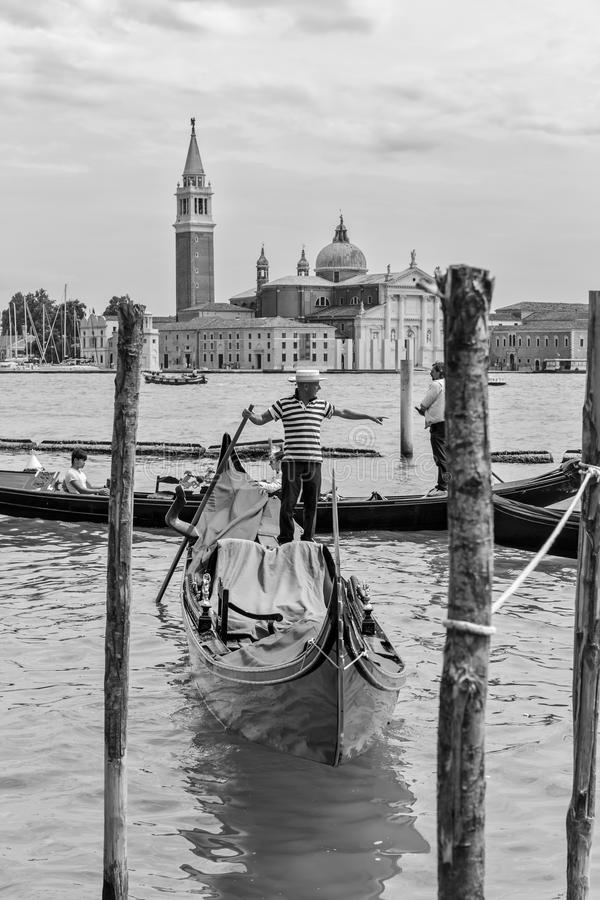 Gondolier rides gondola. VENICE, ITALY - 26 JUNE, 2014: Gondolier rides gondola. The profession of gondolier is controlled by a guild, which issues a limited stock photos