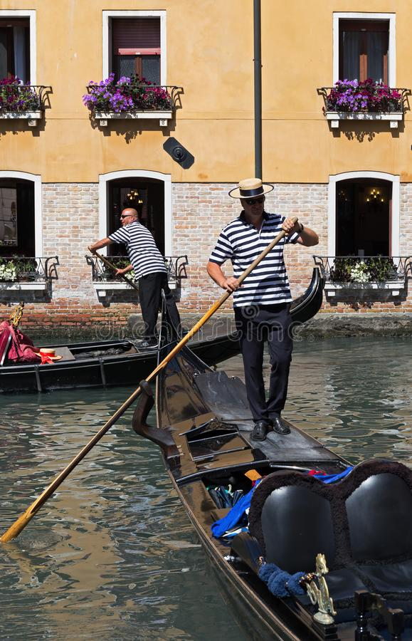 Gondolier rides gondola. VENICE, ITALY - 26 JUNE, 2014: Gondolier rides gondola. The profession of gondolier is controlled by a guild, which issues a limited stock image