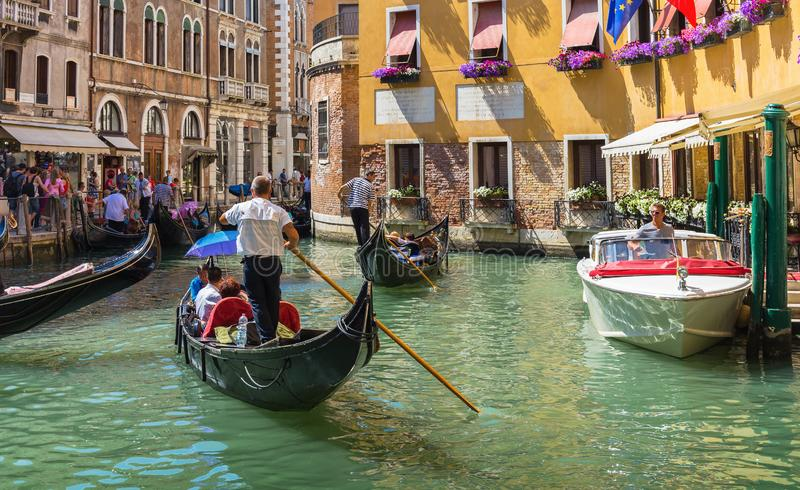 Gondolier rides gondola. VENICE, ITALY - 26 JUNE, 2014: Gondolier rides gondola. The profession of gondolier is controlled by a guild, which issues a limited stock images