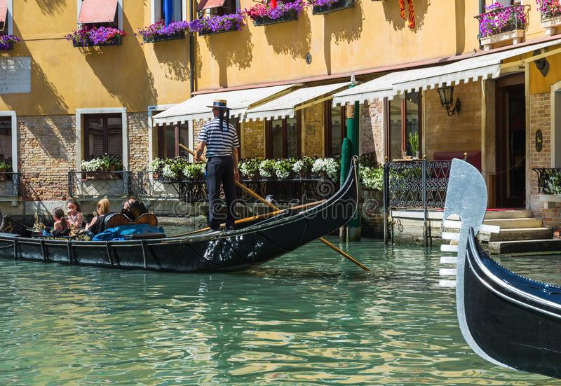 Gondolier rides gondola. VENICE, ITALY - 26 JUNE, 2014: Gondolier rides gondola. The profession of gondolier is controlled by a guild, which issues a limited royalty free stock photos