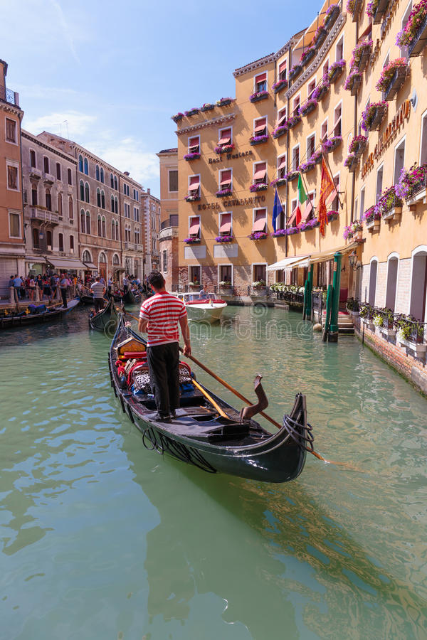 Gondolier rides gondola. VENICE, ITALY - 26 JUNE, 2014: Gondolier rides gondola. The profession of gondolier is controlled by a guild, which issues a limited royalty free stock images