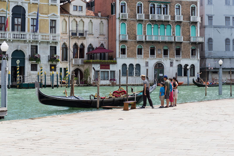 Gondolier rides gondola. VENICE, ITALY - 26 JUNE, 2014: Gondolier and gondola. The profession of gondolier is controlled by a guild, which issues a limited stock image