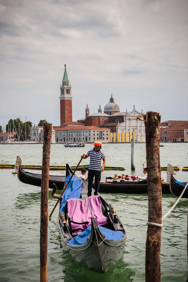 Gondolier rides gondola. VENICE, ITALY - 26 JUNE, 2014: Gondolier rides gondola. The profession of gondolier is controlled by a guild, which issues a limited royalty free stock photography