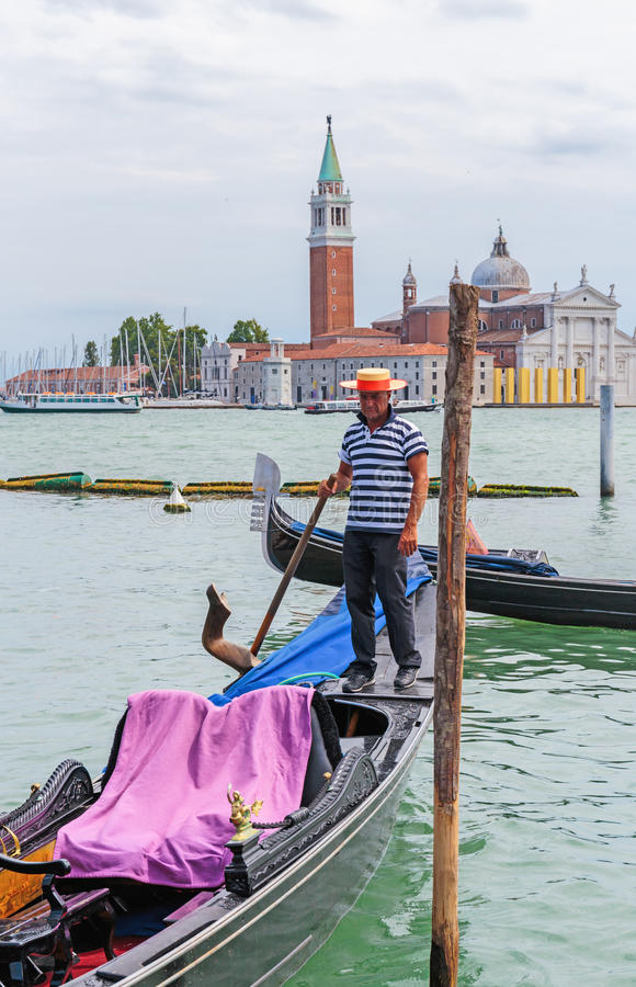 Gondolier rides gondola. VENICE, ITALY - 26 JUNE, 2014: Gondolier rides gondola. The profession of gondolier is controlled by a guild, which issues a limited stock photography