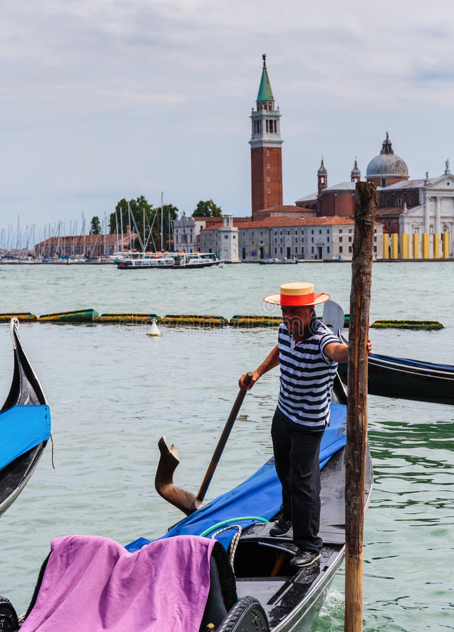 Gondolier rides gondola. VENICE, ITALY - 26 JUNE, 2014: Gondolier rides gondola. The profession of gondolier is controlled by a guild, which issues a limited royalty free stock image
