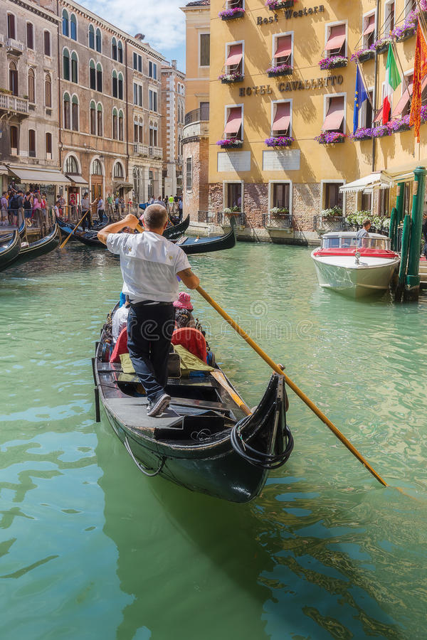 Gondolier rides gondola. VENICE, ITALY - 26 JUNE, 2014: Gondolier rides gondola. The profession of gondolier is controlled by a guild, which issues a limited royalty free stock photo